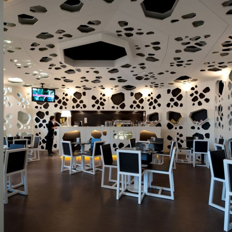 unique-concept-interior-of-a-coffee-shop-with-irregular-shapes-of-cheese-texture-in-white-color-wall-and-ceiling